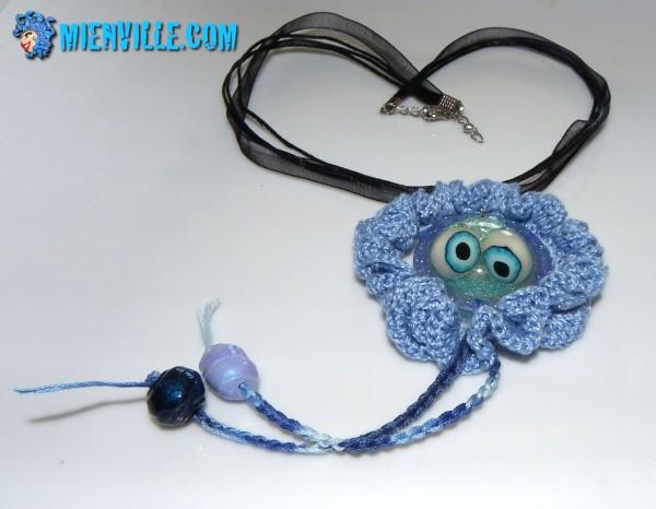 pendentif méduse en fimo et résine dans fraise au crochet, coton bleu clair