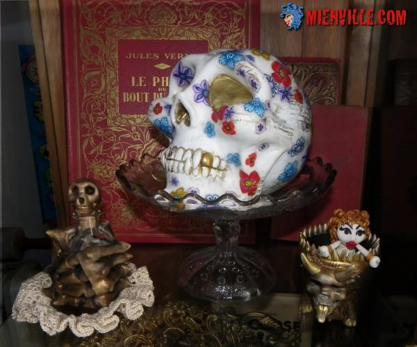 sculpture crane fimo fluo fleuri dans fruitier de verre avec veux livres main décharnée et pot diabolique